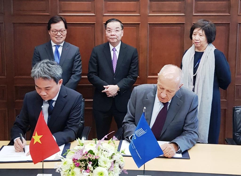 Cục trưởng Đinh Hữu Phí và Tổng giám đốc WIPO Francis Gurry tại lễ ký kết Thỏa thuận hợp tác về Môi trường sở hữu trí tuệ kiến tạo trước sự chứng kiến của Bộ trưởng Chu Ngọc Anh